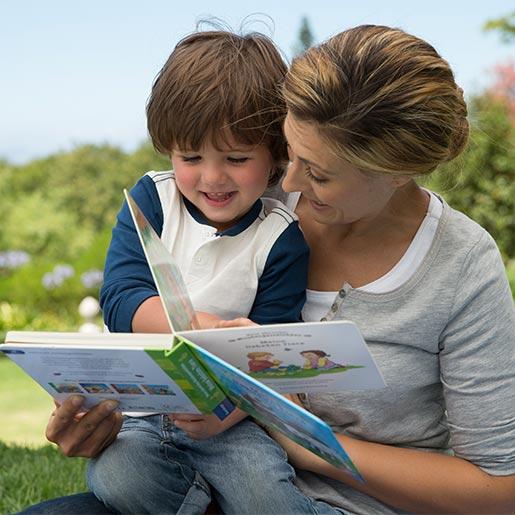 Mutter ließt Sohn ein Pappbilderbuch vor