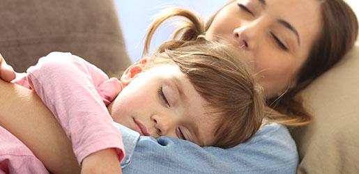 Kind schl?ft in Armen der Mutter